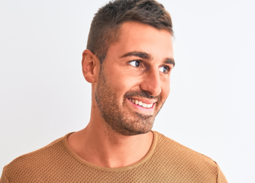 Man wearing a gold sweater against a white background
