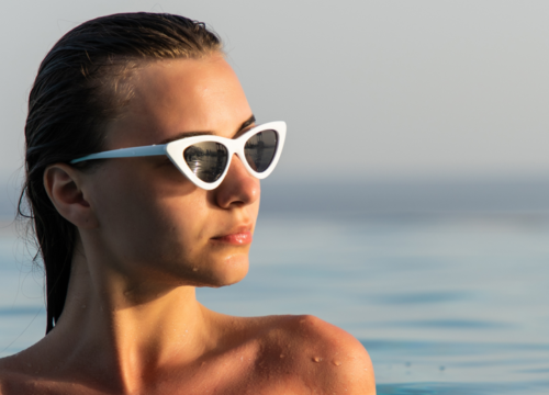 Woman wearing sun glasses in a body of water