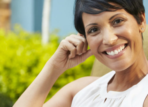 Woman sitting and smiling outside