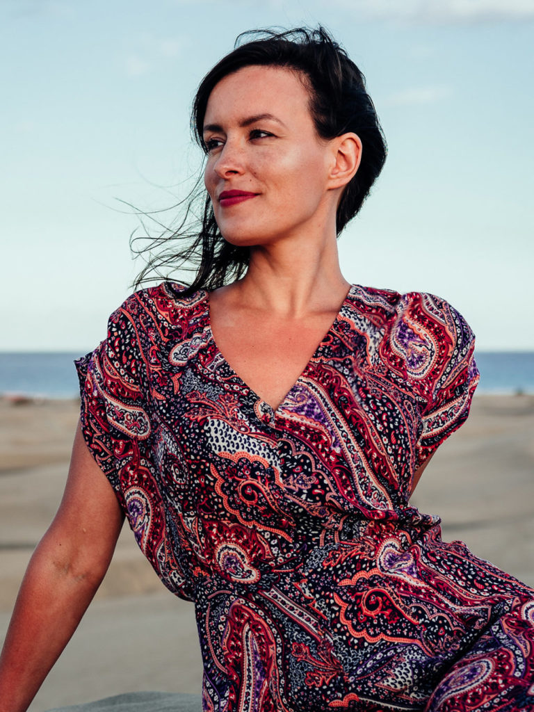 Woman in a red dress at the beach